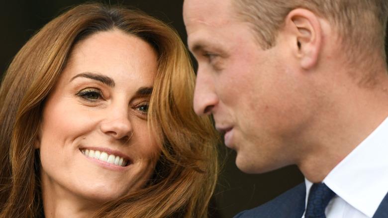 Kate Middleton smiler og prins William snakker