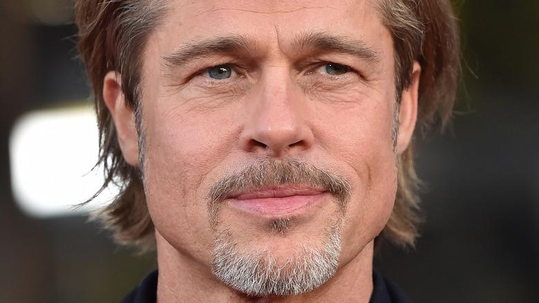 Brad Pitt har et skittent, grått skjegg som smiler
