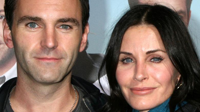 Johnny McDaid og Courteney Cox smiler