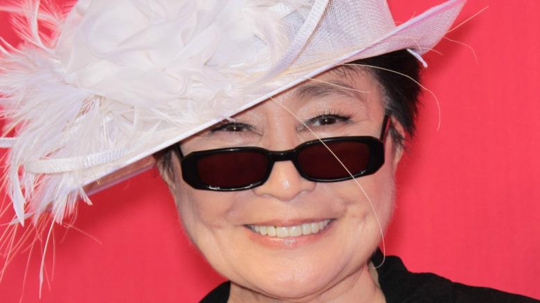 Yoko Ono smiler i solbriller og en fjærhatt