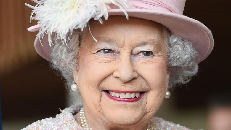 Dronning Elizabeth smilende og iført rosa hatt