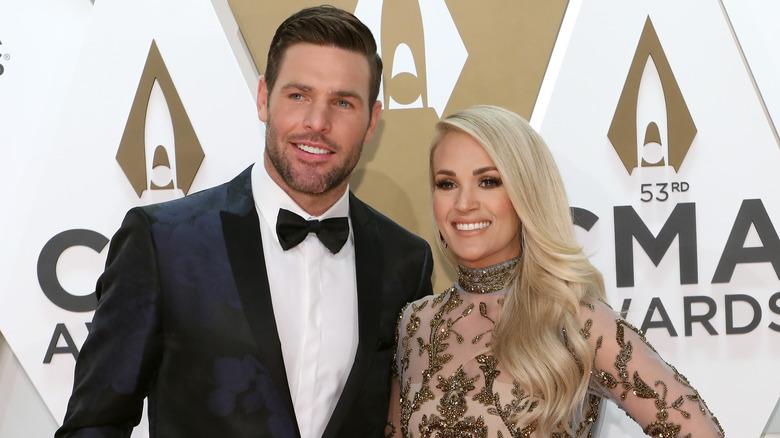 Carrie Underwood og Mike Fisher smiler på den røde løperen