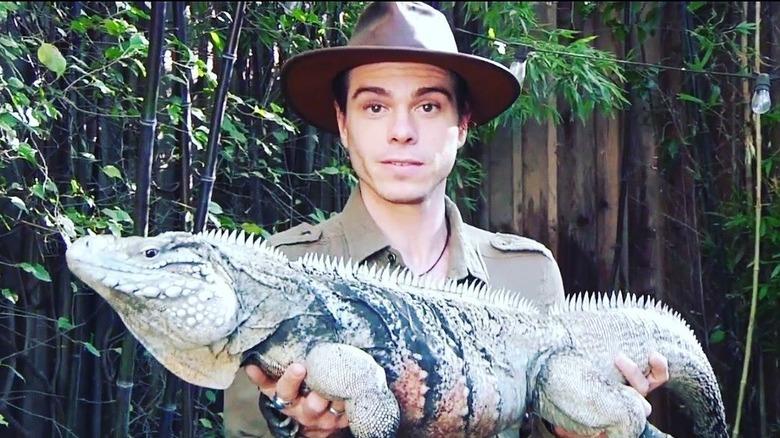 Matthew Lawrence, iført en hvit t-skjorte, bakoverlue, briller, med et reptil