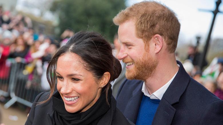 Harry og Meghan smiler utenfor på et offentlig arrangement
