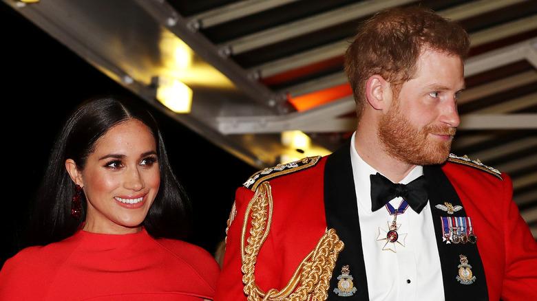 Meghan Markle og prins Harry har på seg rødt og smiler på arrangementet