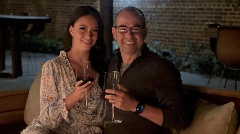 Melyssa Davies og James Murray smiler med glass vin