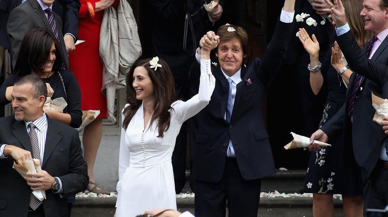 Paul McCartney og Nancy Shevell, begge smilende med hendene i været