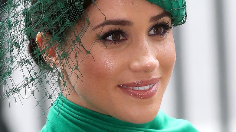 Meghan Markle smiler i grønn fascinator