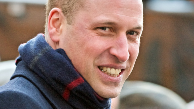 Smilende prins William iført skjerf