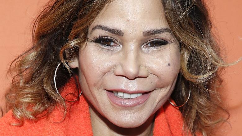 Daphne Rubin-Vega, smilende, krøllete hår ned, mot en oransje bakgrunn, 2020-bilde
