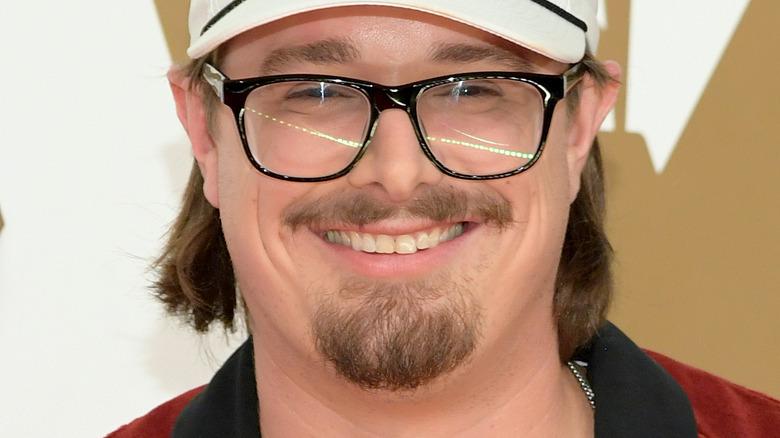 HARDY, smilende, på et rødt teppe, iført briller, iført en hvit hatt, ansiktshår