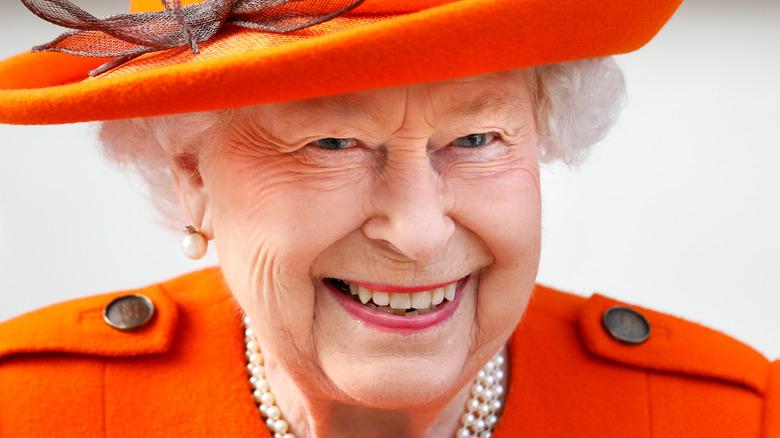 smilende dronning Elizabeth II kledd i oransje