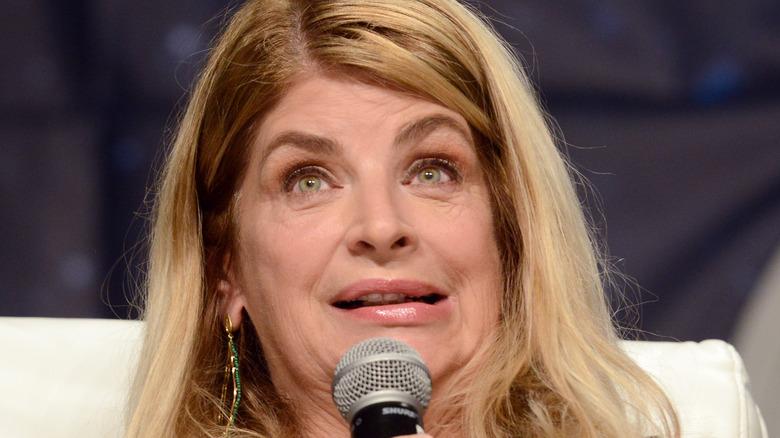 Kristie Alley snakker inn i en mikrofon på scenen