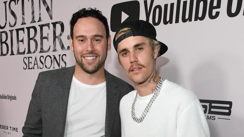 Scooter Braun og Justin Bieber smilende på den røde løperen