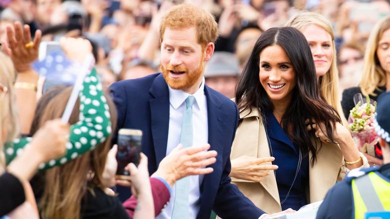 Prins Harry og Meghan Markle hilser til en mengde
