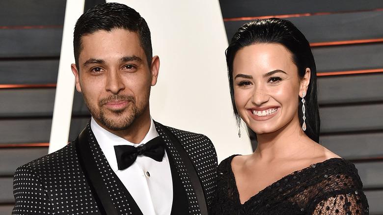 Wilmer Valderrama og Demi Lovato smiler på rød løper