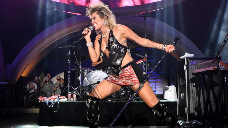 Miley Cyrus på scenen synger inn i mikrofonen