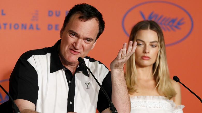 Quentin Tarantino snakker, Margot Robbie bak seg