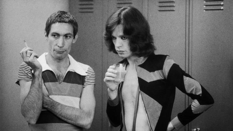 Charlie Watts og Mick Jagger, begge står og lytter