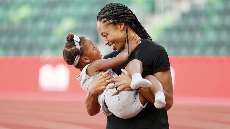 Allyson Felix, holder datteren Camryn på banen