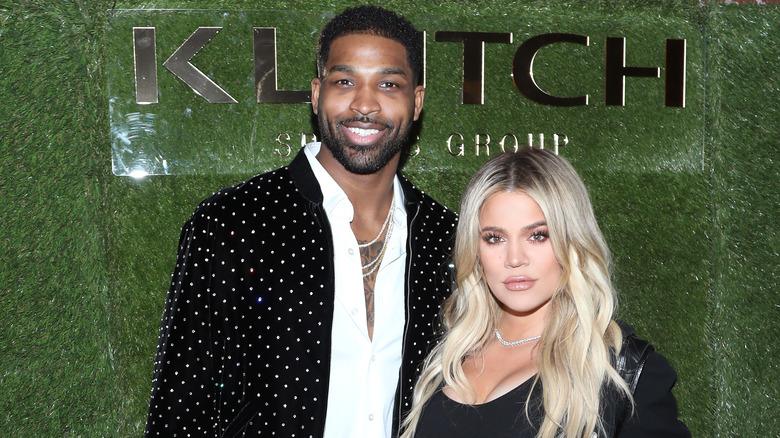 Khloé Kardashian poserer med Tristan Thompson foran en grønn bakgrunn