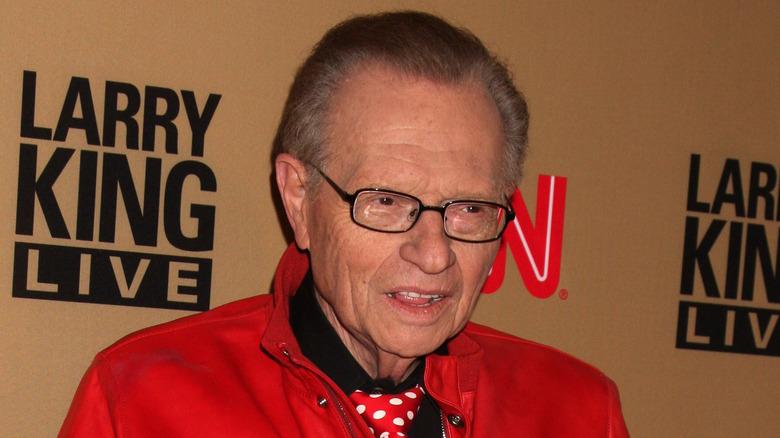 Larry King poserer i rød jakke