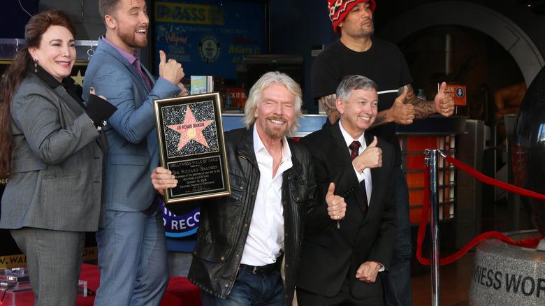Richard Branson smiler og gir tommelen opp og holder Hollywood-stjernen