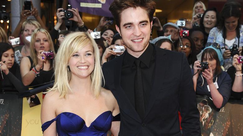 Reese Witherspoon og Robert Pattinson smiler på den røde løperen