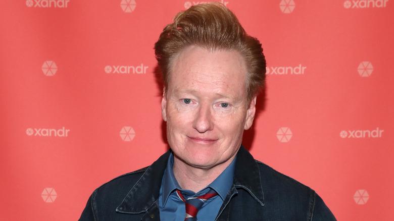 Conan O'Brien i stripete slips, smilende