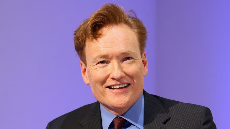 Conan O'Brien i rødt slips og ler