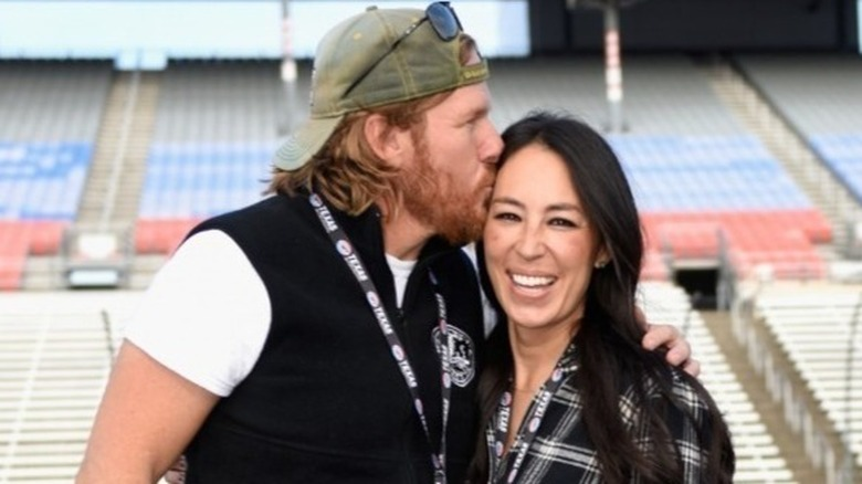 Chip Gaines i baseball hatt kyssende kone Joanna