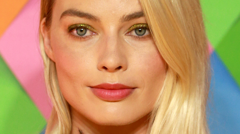 Margot Robbie med lett smil og rosa leppestift