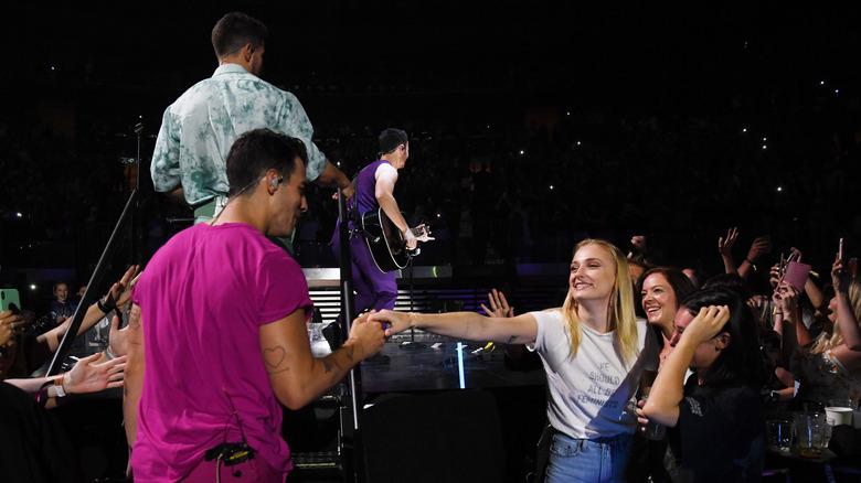 Sophie Turner strekker hånden ut til Joe Jonas på scenen