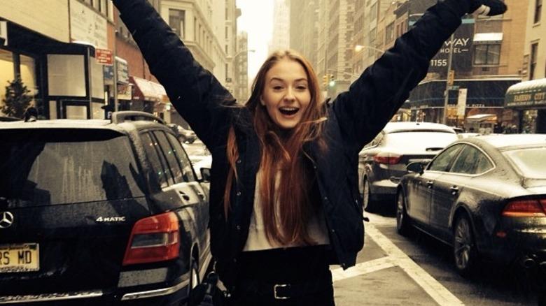 Sophie Turning stående i en by med hendene oppe