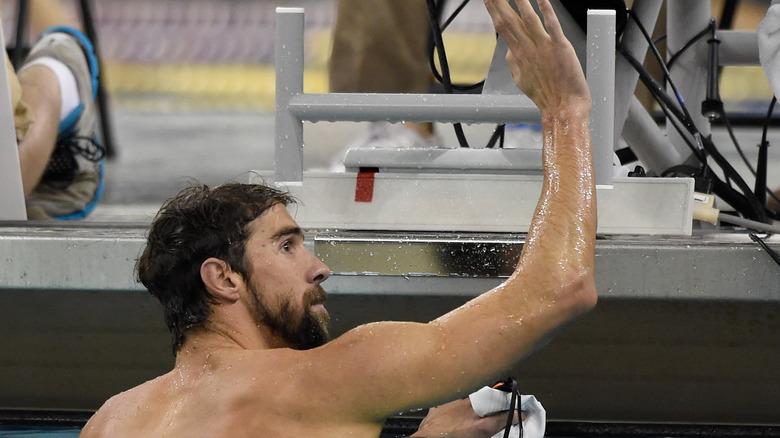 Michael Phelps vinker til en fan i bassenget