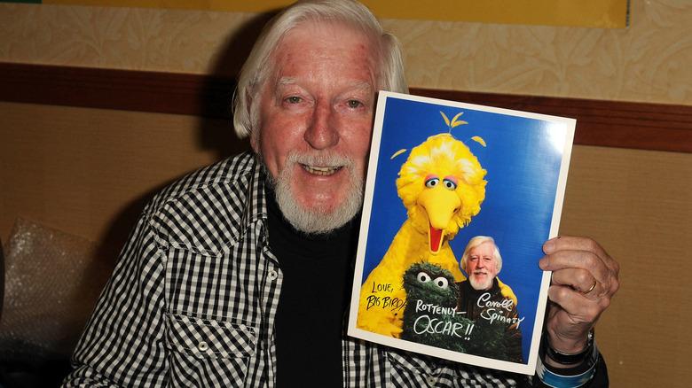 """Carroll Spinning poserer med et headshot av karakterene hans fra """"Sesame Street"""""""