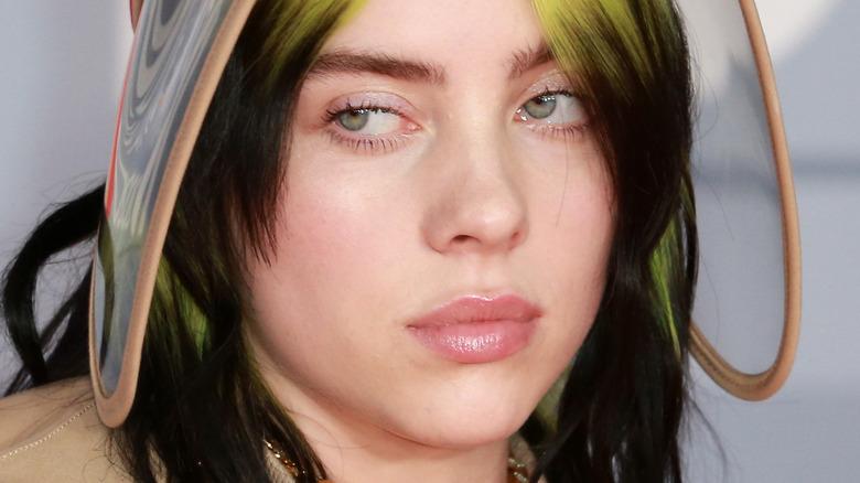 Billie Eilish med grønt hår og visir som ser til siden