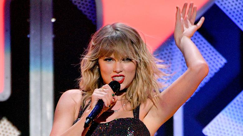 Taylor Swift synger og holder armen opp