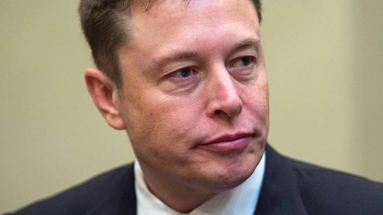 Elon Musk på en konferanse som ser på siden med et seriøst uttrykk