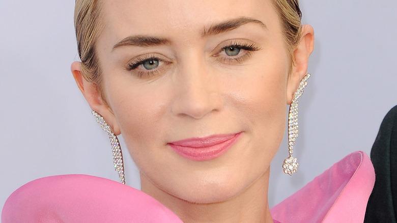 Emily Blunt ser på kameraet med et lite smil og rosa leppestift