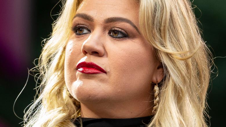Kelly Clarkson ser på siden med alvorlig uttrykk
