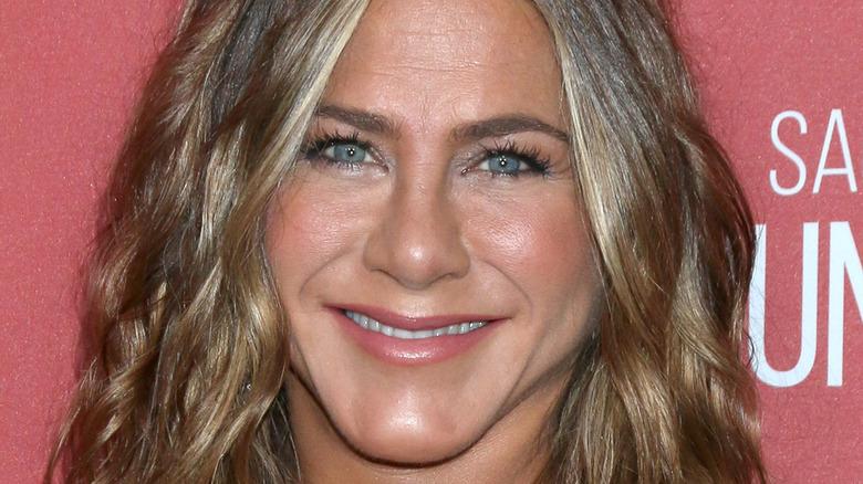 Jennifer Aniston ser på kameraet med et bredt smil