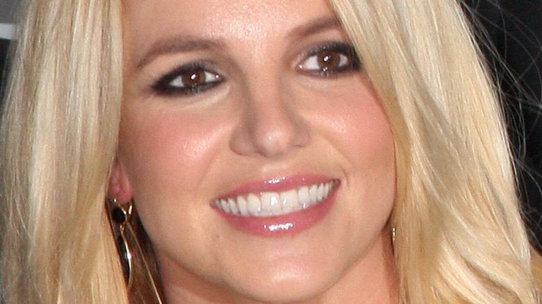 Britney Spears smiler og ser til siden