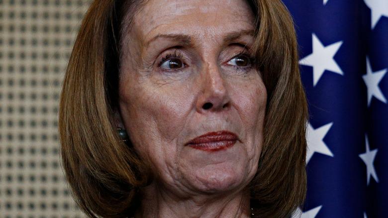 Nancy Pelosi ser til siden foran amerikansk flagg
