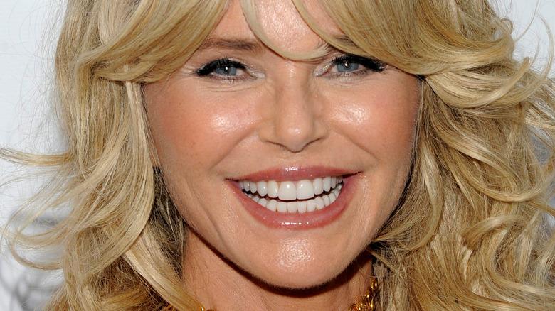 Christie Brinkley smiler med bølget hår og smell