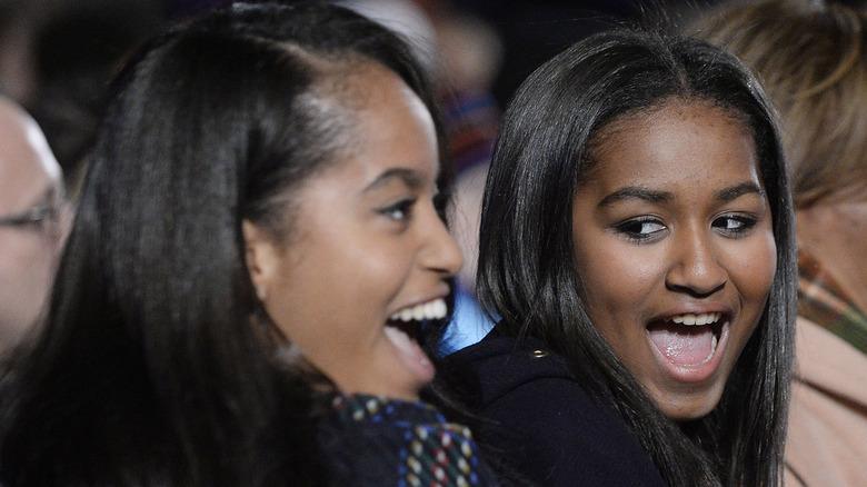 Malia og Sasha Obama smiler på et arrangement