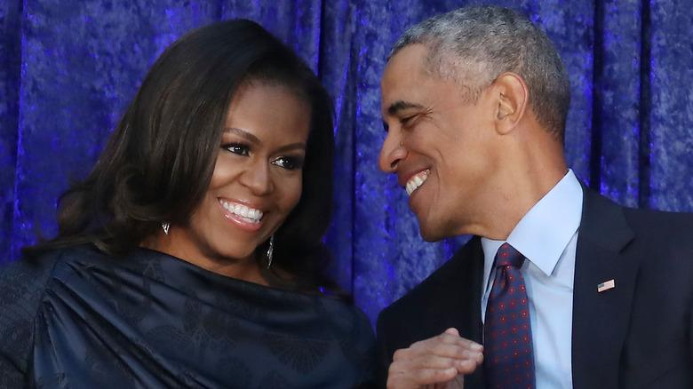 Barack og Michelle Obama smiler på et arrangement