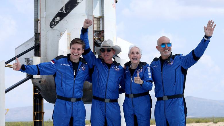 Jeff Bezos og team vinker foran rakett
