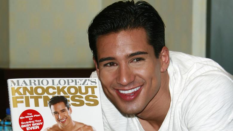 Mario Lopez smiler med treningsboken sin
