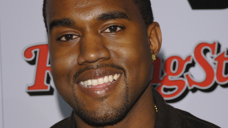 Kanye West smiler på et arrangement